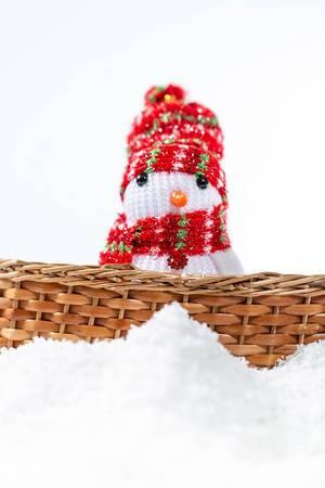 Ein Schneemann aus Stoff mit Mütze und Schal in einem Korb im Schnee