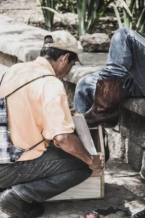 Ein Schuhputzer poliert die Cowboystiefel eines Mannes im Park in Honduras