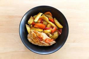 Ein schwarzer Teller mit Hähnchenbrust, Kartoffeln und roter Paprika in der Nahaufnahme