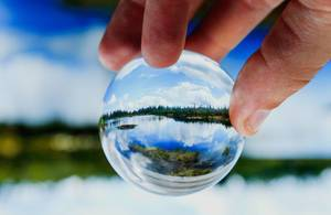 Ein See spiegelt sich in einer Glaskugel