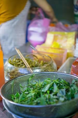Ein Sieb und eine Glasschüssel mit Kräutern auf dem Markt in SAigon