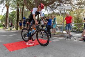 Ein Sportler mit einem roten Helm und der Nummer 112 steigt auf ein Rennrad beim Challenge Triathlon 218 in Peguera