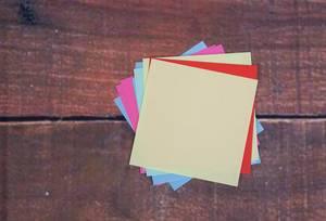 Ein Stapel leerer Notizzettel in bunten Farben, auf einem hölzernen Untergrund