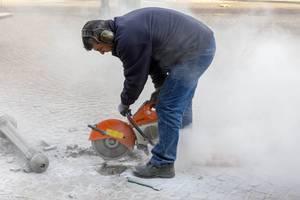 Ein Straßenarbeiter schneidet mit einer Steinsäge in den Gehweg in Venlo