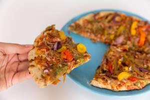 Ein Stück knusprig gebackene vegetarische Pizza von Garden Gourmet in der Hand und bereit zum Verzehr