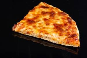 Ein Stück Pizza Margherita spiegelt sich auf schwarzem Hintergrund
