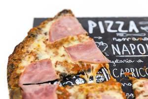 Ein Stück Pizza mit Prosciutto und schwarzem Pizzaboden in der Nahaufnahme