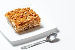 Ein Stück selbstgemachter Honigkuchen auf einem weißem Teller mit Löffel auf weißem Hintergrund