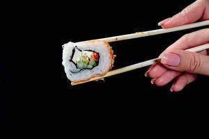 Ein Stück Sushi mit Essstäbchen gehalten