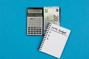 Ein Taschenrechner mit Geld und einem Notizheft für die Berechnung des Budgets für das Jahr 2019