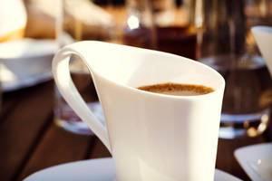 Ein Tasse Kaffee mit geschwungenem Henkel
