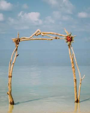 Ein Torbogen oder Hochzeitsbogen aus Treibholz am Strand, mit türkisem Meer im Hintergrund