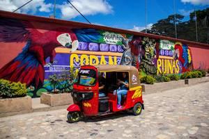 Ein Tuk-Tuk Taxi in Honduras fährt an einem Copan Ruinas Graffiti in Honduras vorbei