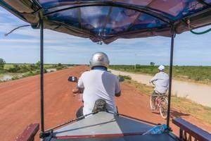 Ein TukTuk überholt einen Mann auf dem Fahrrad in Siem Reap