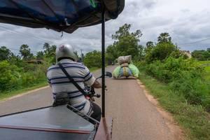 Ein überladendes Motorrad fährt vor einem Tuk-Tuk in Siem Reap
