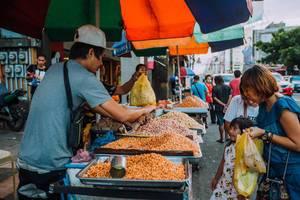 Ein Verkäufer verkauft geröstete Nüsse auf einem Markt