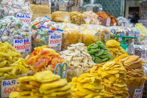 Ein Verkaufsstand mit Süßigkeiten und kandierten Früchten auf dem Ben Thanh Markt in Saigon