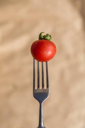 Ein vertikales Foto einer kleinen roten Tomate auf einer Gabel
