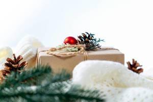 Ein Weihnachtsgeschenk mit roter Christbaumkugel mit einer weißen Strickdecke
