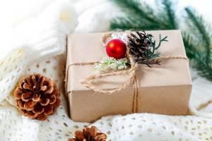 Ein Weihnachtsgeschenk mit roter Christbaumkugel und Tannenzapfen geschmückt liegt auf einer weißen Strickdecke