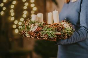 Ein Weihnachtskranz mit Tannenzweigen, Zapfen, Äpfeln und Kerzen