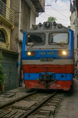 Ein Zug fährt durch eine Enge Gasse in Hanoi, Vietnam