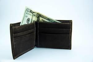 Ein zwanzig Dollarschein guckt aus einem dunkel brauen Lederportemonnaie heraus