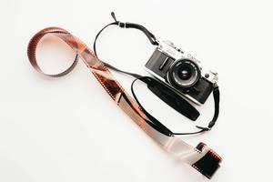 Eine alte Canon AE-1 Foto-Kamera mit einem Film auf weißem Hintergrund