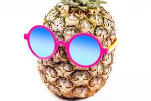 Eine Ananas trägt eine rosa Sonnenbrille vor weißem Hintergrund