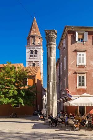 Eine antike römische Säule mit einer Kirche im Hintergrund in Zadar, Kroatien
