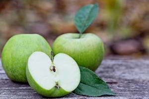 Eine Apfelhälfte mit zwei günen Äpfeln im Hintergrund