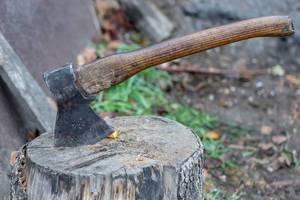 Eine Axt steckt in einem Holzpflock