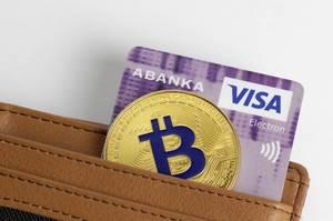 Eine Bitcoin-Münze mit einer VISA-Karte in einer Geldbörse