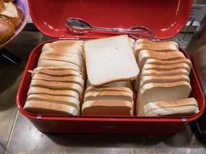 Eine Box mit weißem Toastbrot an einem Buffet