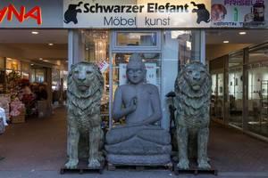 Eine Buddhastatue und Löwenstatuen vor einem Möbelgeschäft