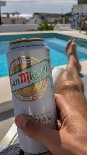Eine Dose San Miguel Bier in der Hand eines Mannes der an einem Pool auf Mallorca entspannt