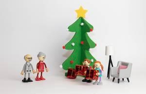 Eine Familie feiert Weihnachten - Holzfiguren mit einem Weihnachtsbaum