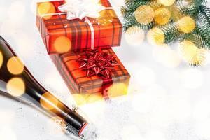 Eine Flasche Champagner und zwei Geschenkboxen - Das Konzept von Weihnachten vor einem Schneehintergrund mit bokeh und Tannenzweigen