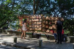 Eine Frau betrachtet die aus Kork gefertigten Handtaschen eines Souvenirstandes