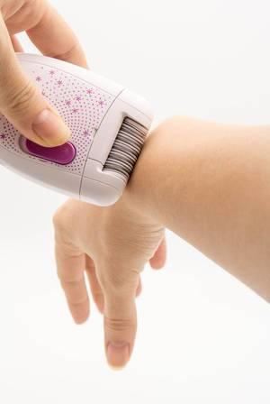 Eine Frau entfernt sich die Haare vom Arm mit einem Epiliergerät