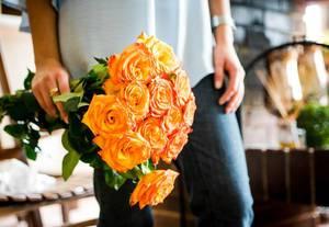 Eine Frau hält einen Bund orangene Rosen
