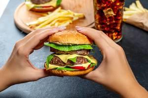 Eine Frau hält einen doppelten Burger in ihren Händen, mit Fast-Food im Hintergrund