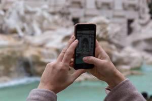 Eine Frau macht ein Foto mit dem iPhone von Statuen in Rom