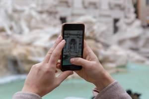 Eine Frau macht ein Foto mit dem Smartphone am Palazzo di Venezia in Rom