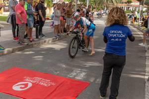 Eine Frau mit blau-weißem Anzug und der Nummer 51 schwingt sich auf ihr Rad beim Challenge Triathlon 2018