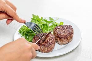 Eine Frau mit Messer und Gabel in ihren Händen, schneidet eine Fleischbulette