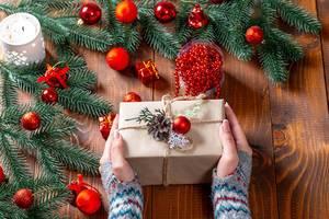 Eine Frau mit Stulpen an den Händen hält ein Weihnachtsgeschenk, umgeben von Tannenzweigen und roten Weihnachtsbaumkugeln