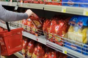 Eine Frau nimmt eine Packung Nudeln aus dem Regal eines Supermarktes