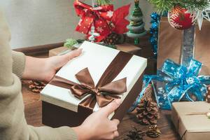 Eine Frau packt einen Geschenkkarton mit brauner Schleife unter den Weihnachtsbaum