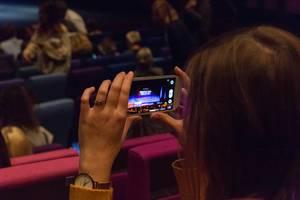 Eine Frau schießt ein Foto mit einem Smartphone von der Bühne des TEDxVenlo Events 2018